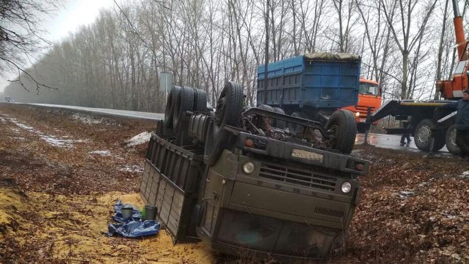 В Таловском районе на заснеженной дороге перевернулся КамАЗ с зерном